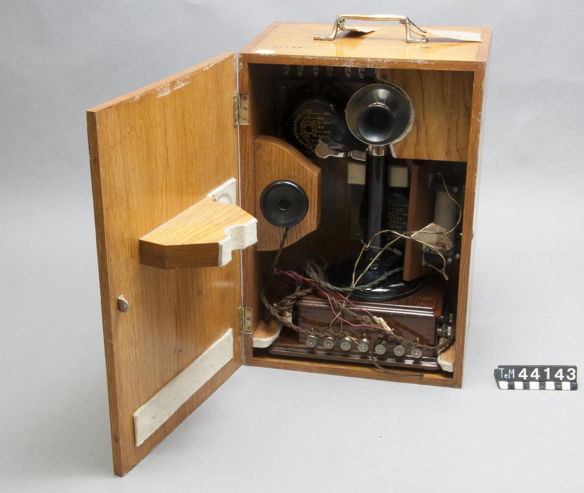 Telefonapparat s.k. ljusstake, i trälåda med två lösa drosslar och två transformatorer på ringkärna träunderdel, med skaft och hörtelefon i bakelit. Fältapparat för CB system.