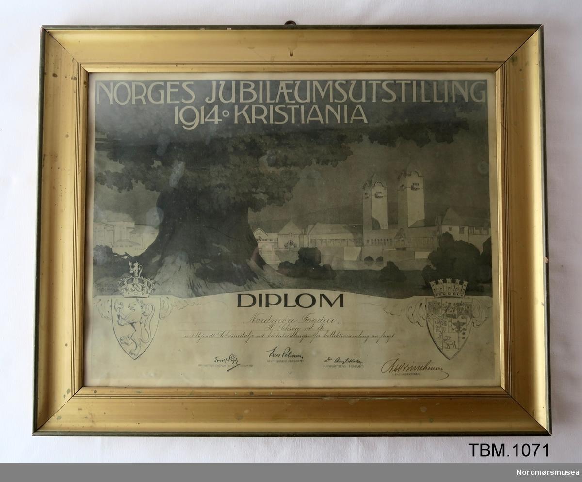 Stort diplom i glas og ramme. Gitt til Nordmøre Fogderi på Jubileumsutstillinga i 1914.