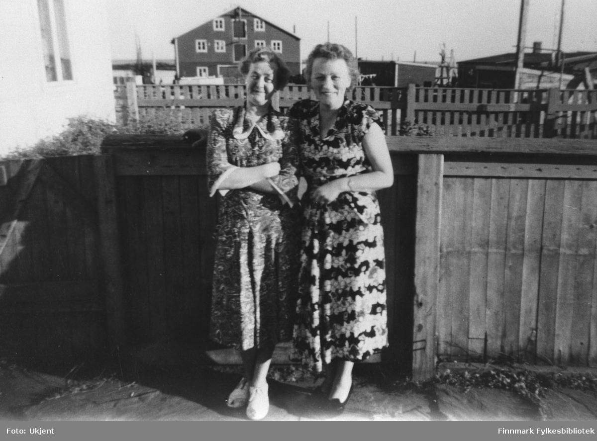 Bildet viser to kvinner. Damen til høyre er Klara Abrahamsen, gift med Thorleif Abrahamsen. Damen til venstre er Laila Aanstad, søster tli Thorleif og gift med Ivar Aanstad fra Vadsø. Bildet er tatt utenfor Abrahamsgården i Kiberg.