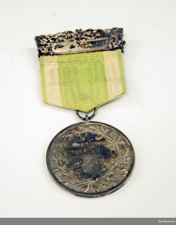"""Medalje (ant. deltakermedalje) med innskrift: """"THELEMARKENS SKIFORBUND"""" og """"I SKIENS SPOR SUNDHED GROR"""" (på framsiden) Bånd i hvitt og lysegrønt - falmet."""