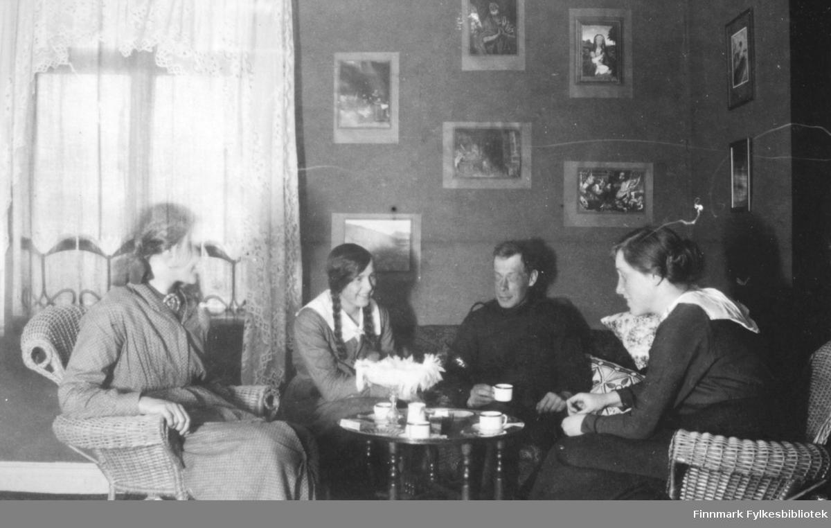 """""""Fredenslund mai 1917"""" lyder teksten i albumet. På bildet ser vi fire ungdommer, tre damer og en mann rundt et bord. Mannen med kaffekoppen på bildet er Hans Julius Gabrielsen. Den unge damen til høyre på bildet er en av hans søstre. Damen til venstre sitter i en kurvstol, hun har på seg en kjole med små prikker og belte i livet, og en brosje i halsen. I sofaen eller divanen sitter en jente med mørke lange fletter, hun er kledd i en kjole med stor, hvit krage. I høyre side av bilde sitter en annen ung kvinne og smiler, hun er kledd i en kjole med hvit krage og belte i livet. Håret er oppsatt i en knute bak. På bordet står det kaffekopper, et stettfat med det som ser ut som en heklet duk og til venstre på bordet ligger en eske, muligens sigaretter eller spillkort? På veggen henger bilder med bibelske motiv, ref. madonna med barnet øverst til høyre. Fredenslund var Lensmann Strands gård, og lå i Bonakas, Tana. Bonakas, nordsamisk: Bonjákas, er en jordbruksbygd beliggende på vestsiden av Tanaelva i Tana kommune omkring ti kilometer ovenfor Tanamunningen."""
