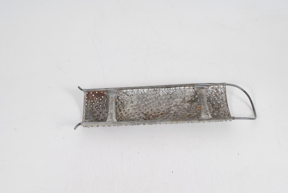 Form: avlange og krummet med bånd/stenger på baksiden og med en bøyle til å holde i
