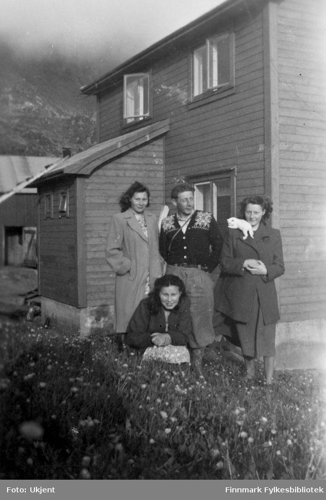 Her poserer jenter fra Bergfjord i Loppa sammen med Aksel Amundsen fra Sør-Tverrfjord. Pikene er fra bakerste rad til venstre: Anna Henriksen, Åse Henriksen og Eli Henriksen. De er kledd i jakker og kjoler. Aksel har på seg en mønstrete genser, knebukser og muligens en veske av noe slag. Åse har en liten kattunge på skulderen. I bakgrunnen kan man se et hus med åpne vindu og grunnmur.