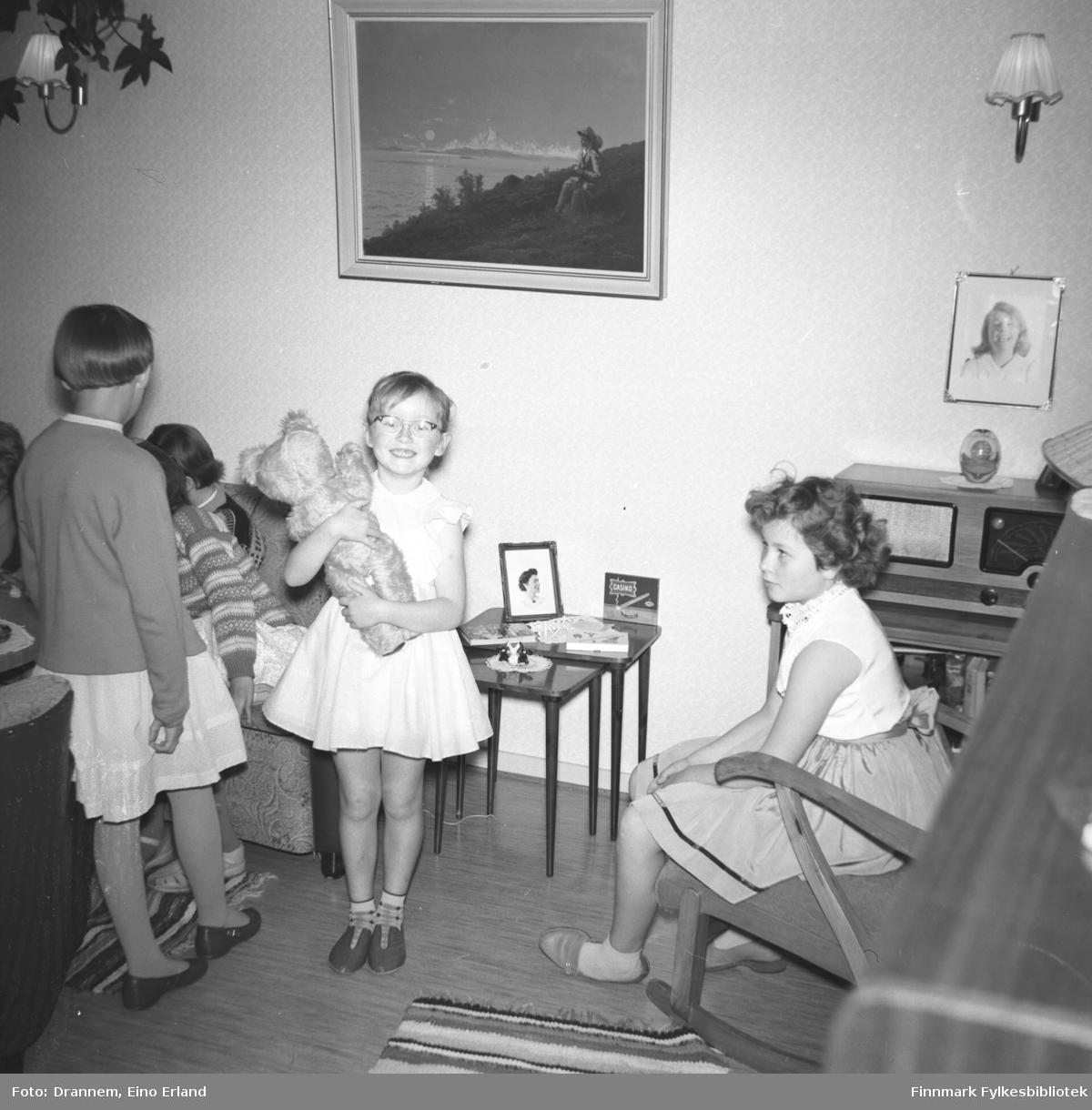 Barn samlet i stuen til familien Drannem i Hammerfest til Turids fødselsdag. Inger Hansen står med en Teddybjørn i armene og Turid sitter i en gyngestol.
