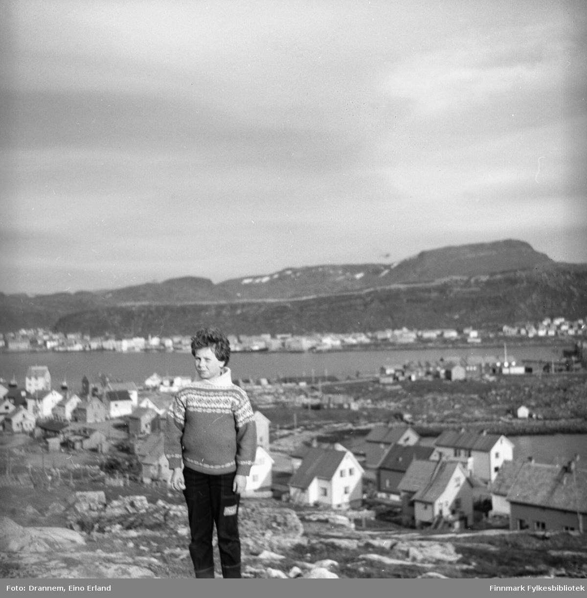 Turid Karikoski fotografert i terrenget ovenfor Fuglenes med Hammerfest senturm i bakgrunnen og Rossmollbukta nede til høyre. Fjellet Tyven ses oppe til høyre. Bldet kan være tatt St. Hans-aften.