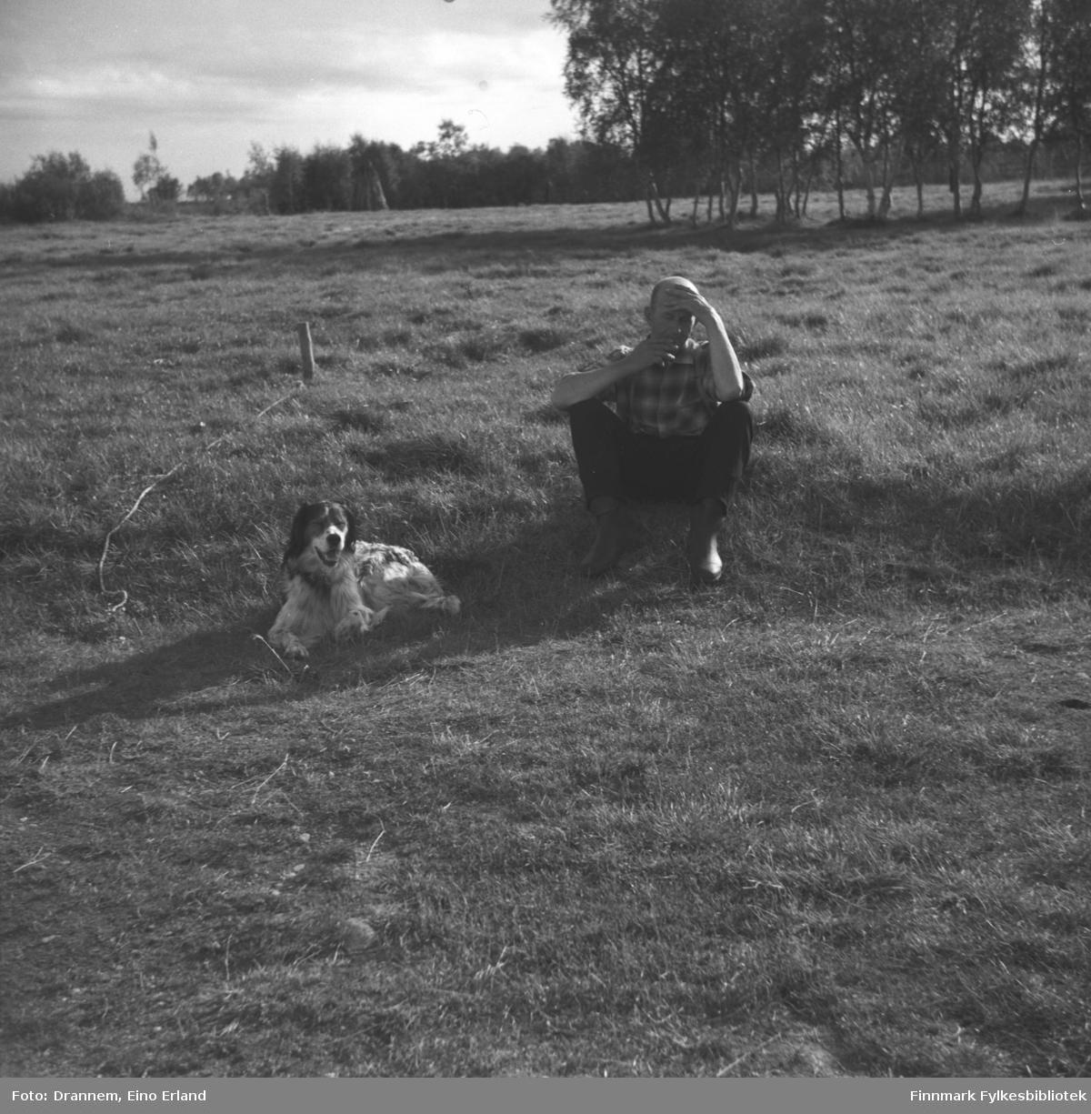 Uuno Lappalainen sitter på et jorde med hunden Rexi ved siden av seg. Stedet er ukjent.