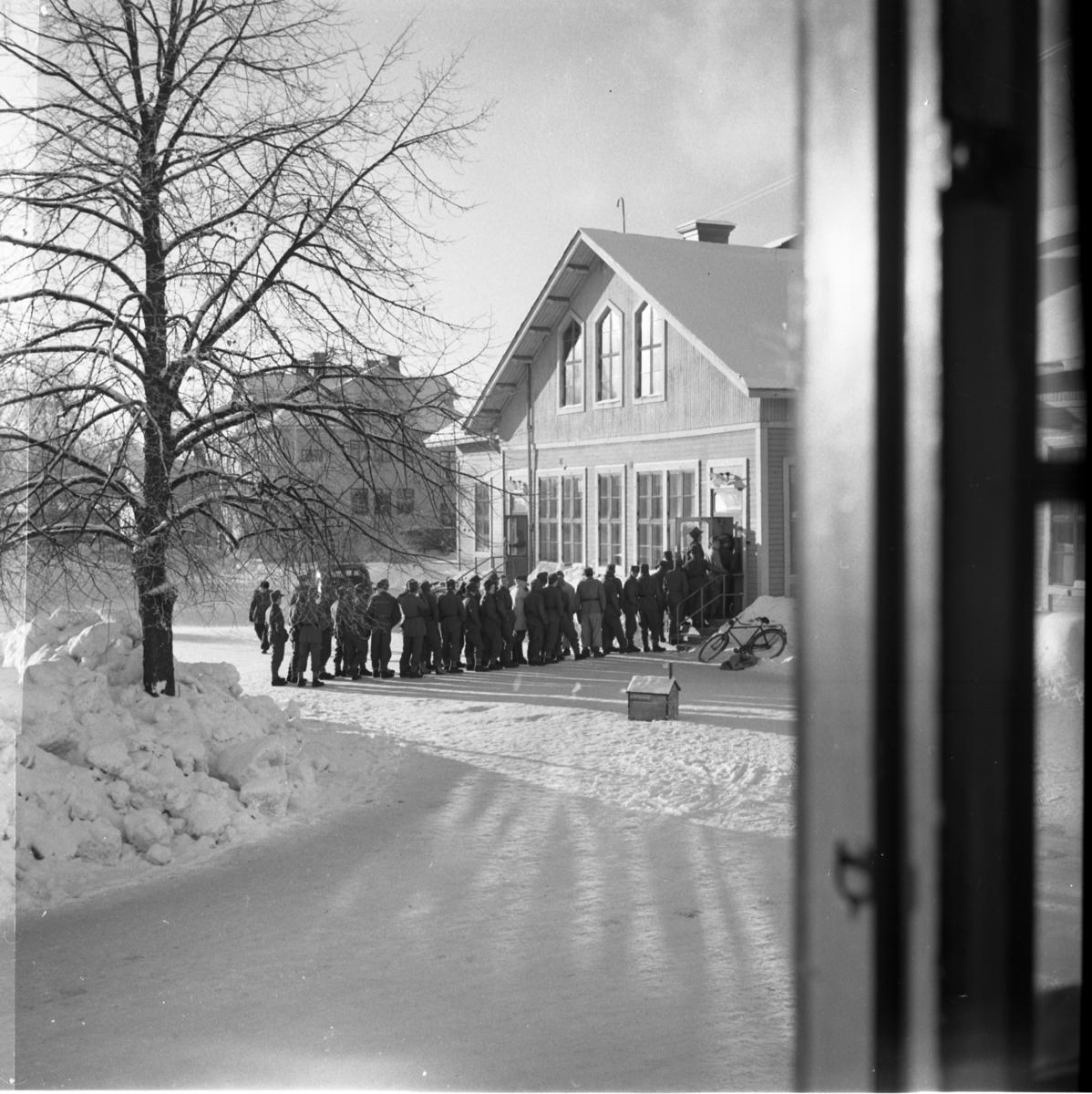 Värnpliktiga i en kö på en vinterdag på Norrlands dragonregemente K4, Umeå, 1955-1956.
