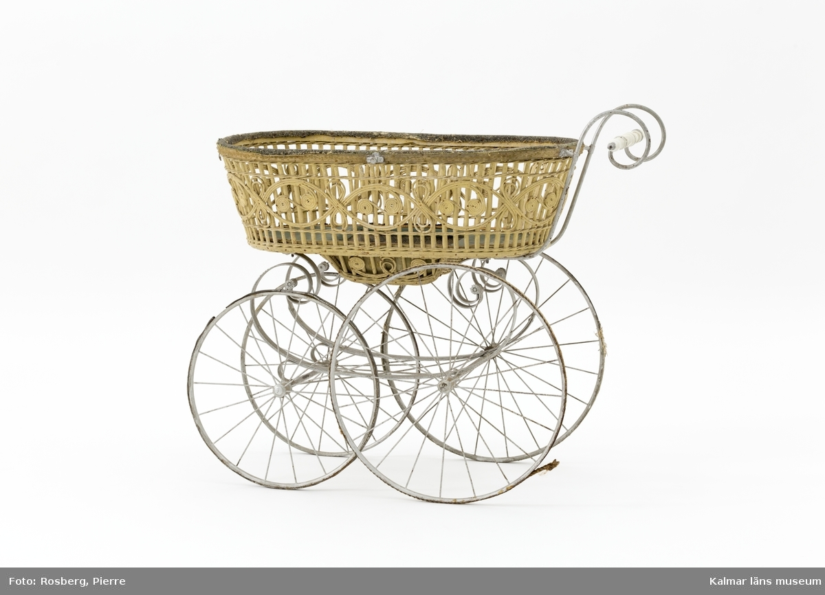 KLM 28338:1. Barnvagn, liggvagn. Hjul och underrede av metall målade i silverfärg, troligen ej ursprunglig. Två hjul är gummiklädda, ett saknar detta och det fjärde är försett med flätat naturmaterial. Handtag av vitt porslin. Vagnskorg med trästomme bestående av flätade stående och liggande spjälor målade i ljusgul nyans. Övre kanten av korgen är klädd med grovt ylletyg och på utsidan ett vävt tygband i gul ylle. Korgens botten är klädd med grönt konstläder och säckväv målat i rutmönster. I mitten av korgen en försänkning. På korgens sidor fästen för sufflett. På hjulen instansat: BRENNABOR D.R.G.M.