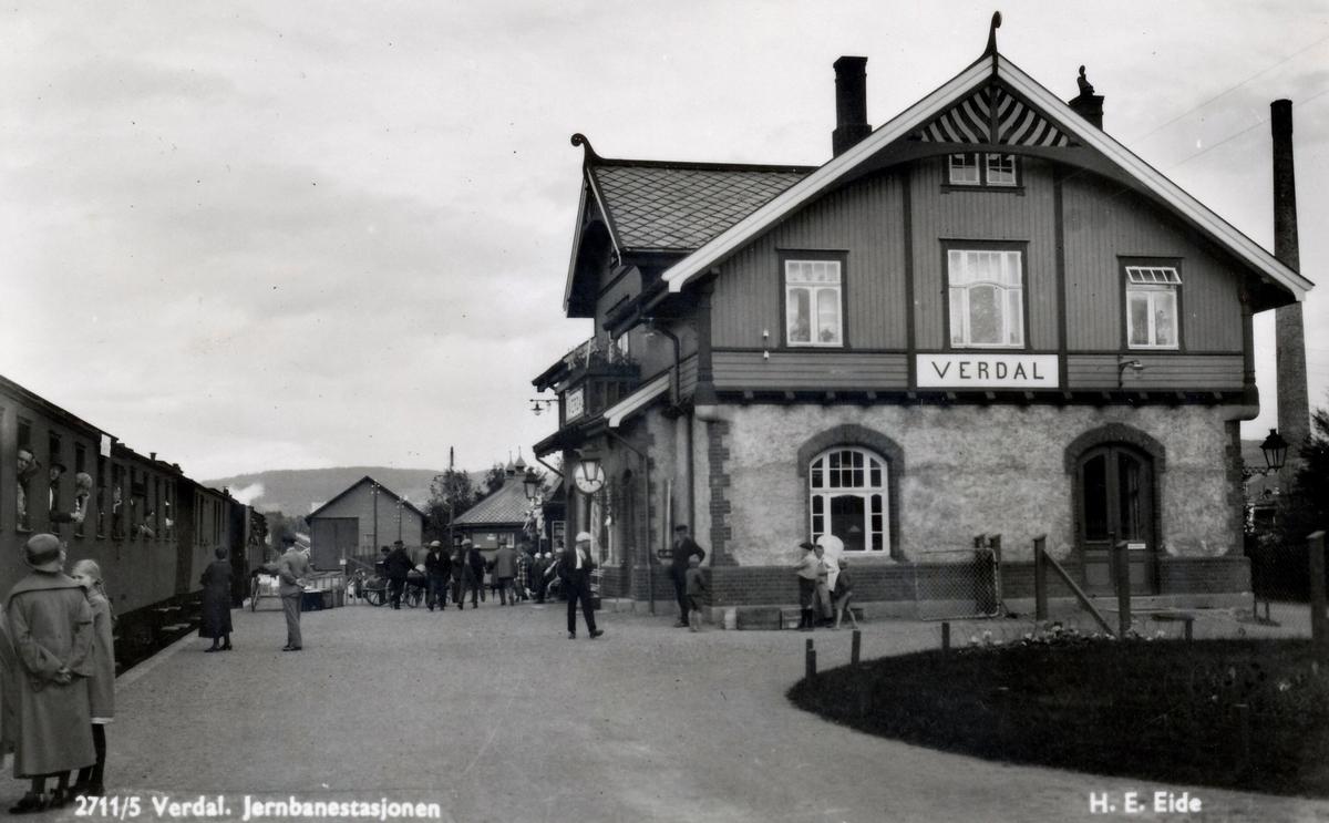 Verdal stasjon med nordgående tog og reisende på plattformen.