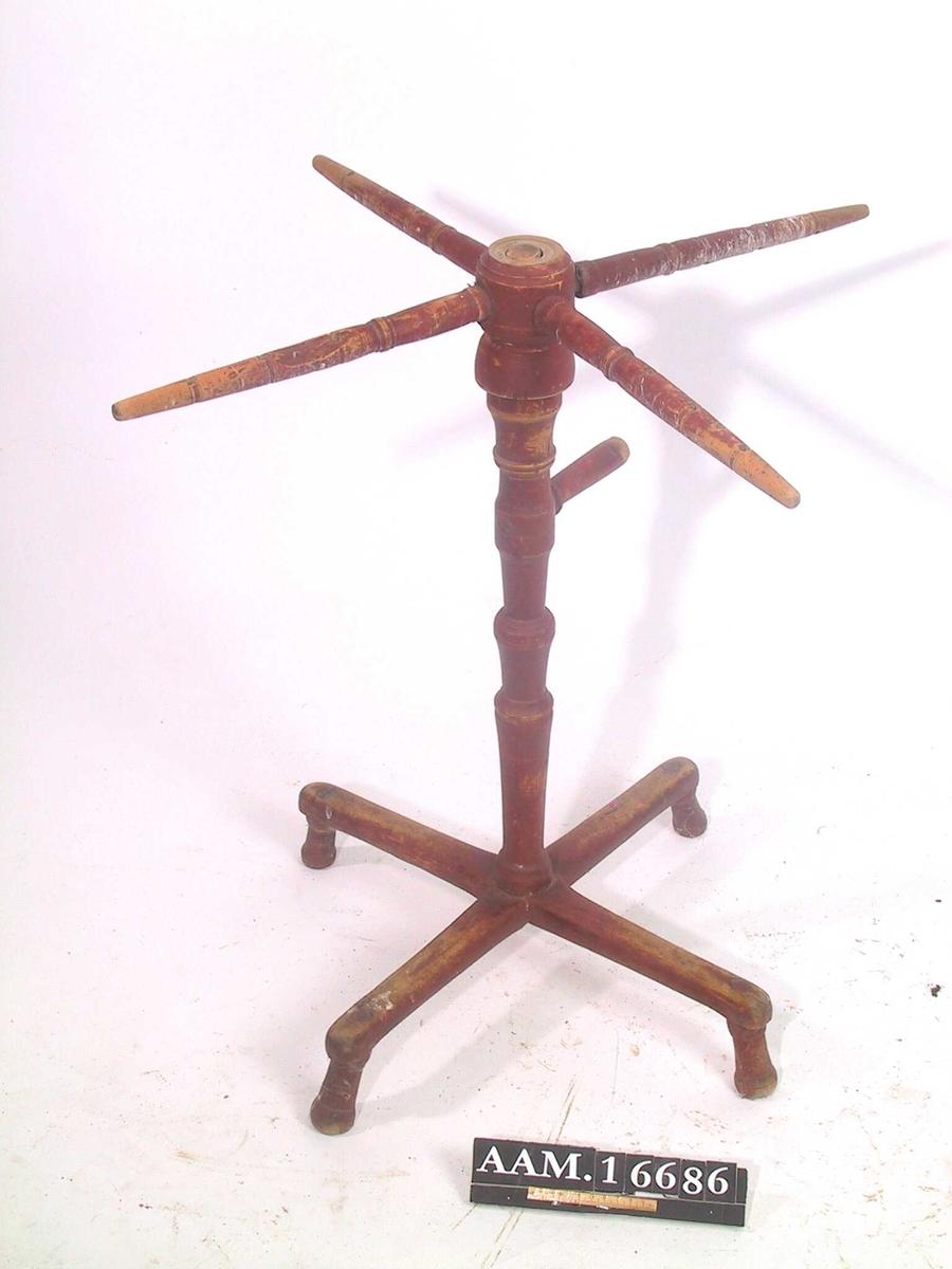 Garnvinne. Tre, malt rødbrun. Korsformet fot på korte dreide ben. Dreid midtstang med skålformet toppstykke på sylindrisk underdel,  hvori er festet fire korsarmer.