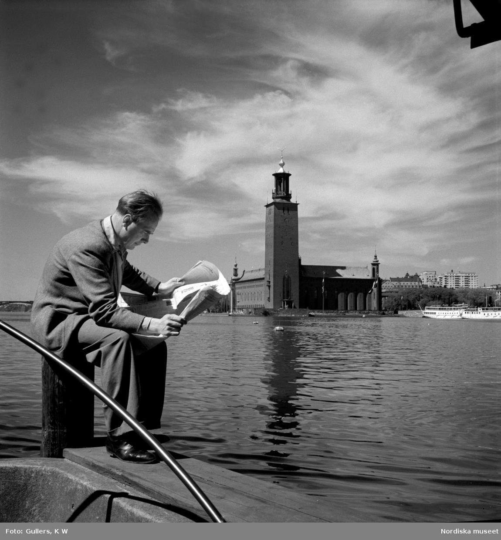 En man sitter på en pollare och läser en tidning. Stockholms stadshus och Riddarfjärden i bakgrunden.