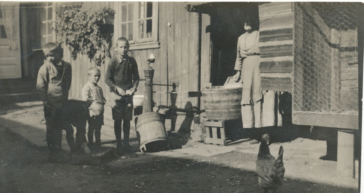 Fire gutter i et gårdsrom. En kvinne vasker.
