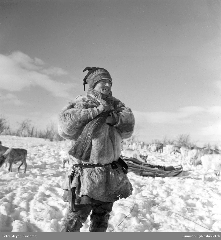 Henrik Andersen Spein kledd i pesk, fotografert på vidda i Kautokeino vinterstid. I bakgrunnen en slede og reinflokken.