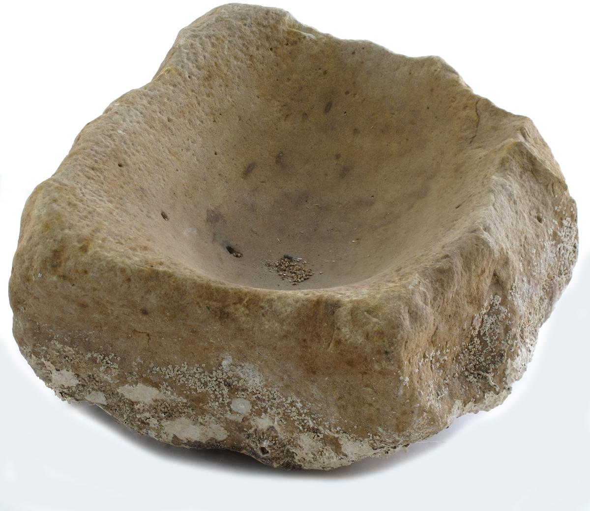 Morter for knusing av mais o. lign. Uthogd steinblokk, fire sider. På tre sider tilnærmet rette, den fjerde  (den ene langside) mer uregelmessig og med  konkav innskjæring i det ene hjørne. Oval blankslitt fordypning innv. Noe skjell eller ruer på den delen som ikke lå nede i bunnen. Sto trolig på dekket av slaveskipet.