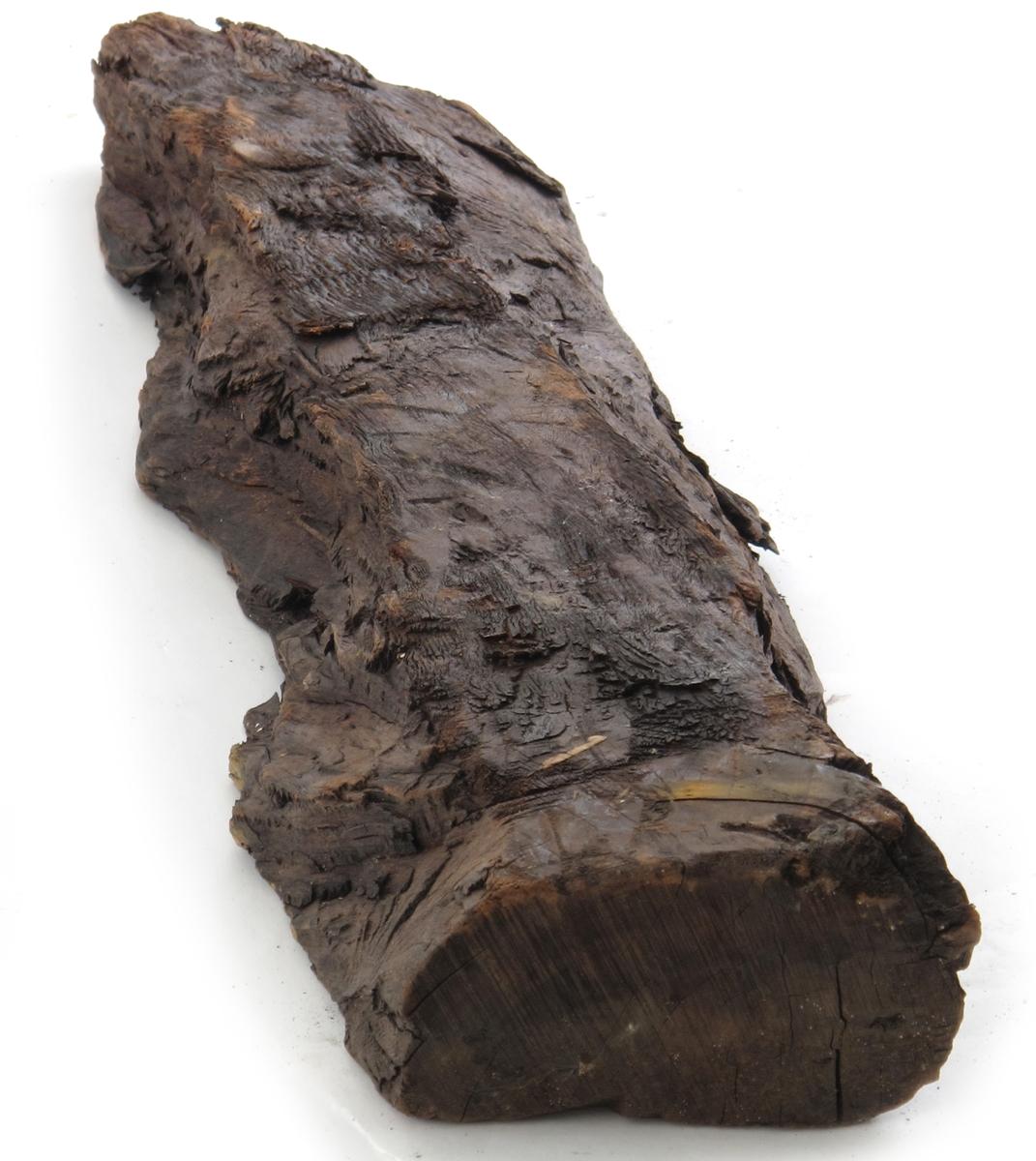 Cuba-mahogny. Liten stykke planke. Flatskåret på begge sider, ikke avrettet langs kantene. Rødlig i flatskårne partier. Avskåret med sag i ene ende, hugget spiss i den andre ende.