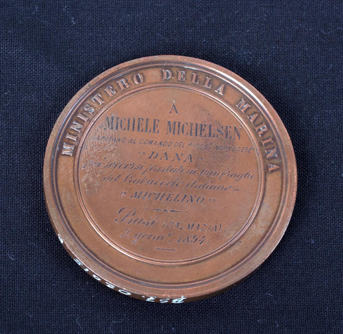 Redningsmedalje gitt til DS DANA for redning av besetning på italienske MICHELINO i 1894. Motiv, siluett av en mann med bart samt tekst rundt.
