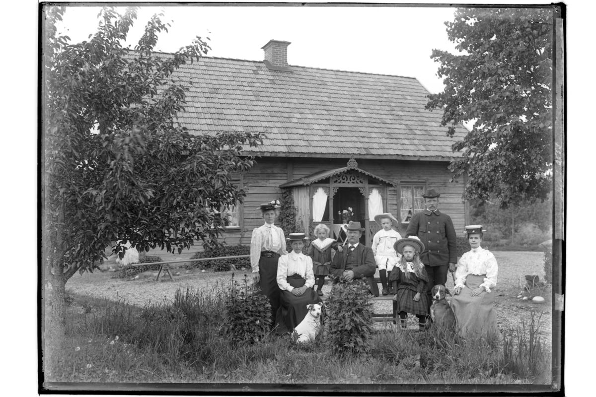 Envånings bostadshus med förstebro med snickarglädje.Åtta personer och två hundar framför huset.Aug. Karlsson