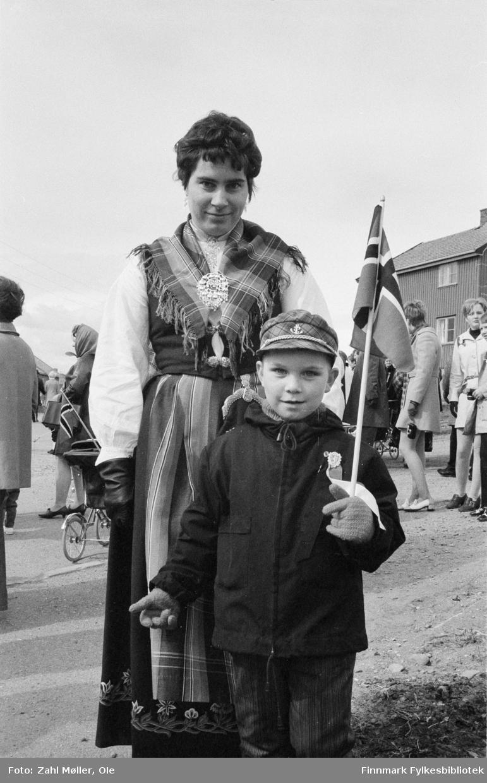 17.mai i Vadsø 1969. Fotografert av Ole Zahl Mölö. Kvinnen er kledd i Nordlandsbunad og gutten holder et norsk flagg. Lua er matrosinspirert med anker og gullsnor.