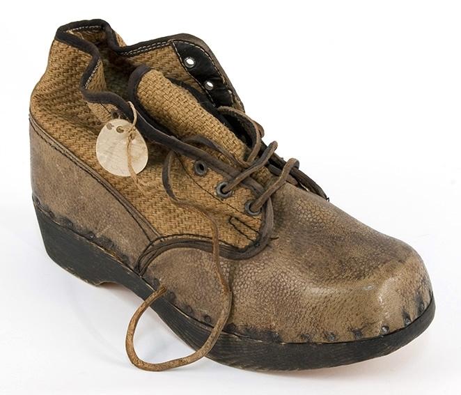 En høy, brun sko, eller lav støvel, med tresåle, lisselukking og overdel av strie (vrist, ankel) lær (hæl, tupp, side nederst. Antatt krigsprodukt.