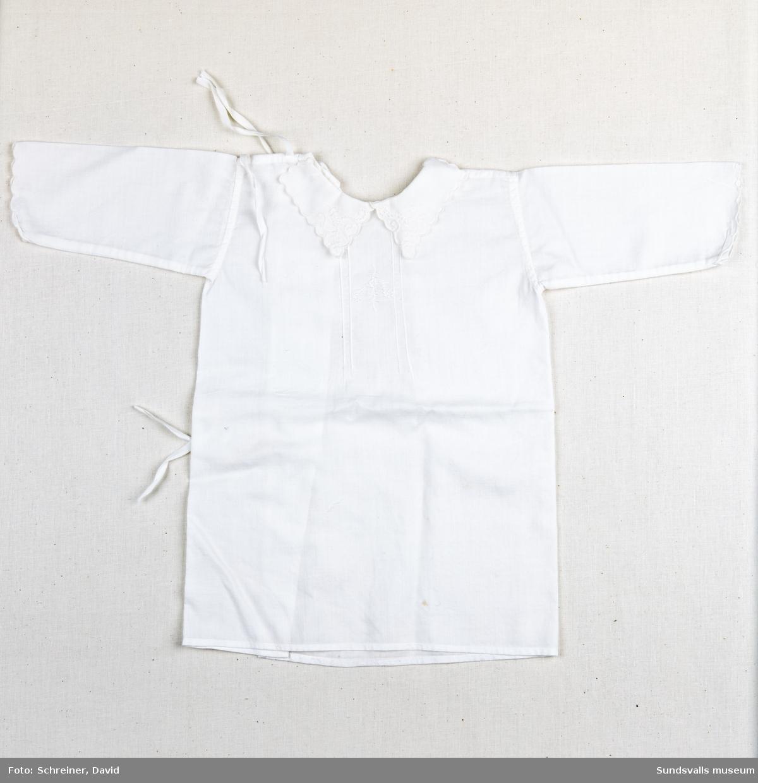 En knytskjorta med lång ärm. Den rundade halsen har dekorerats med en bågformad broderad spetskrage liksom manchetterna. Bröstpartiet bär en broderad blomma och ett bladverk som inramats med ett längsgående sytt linjeverk.