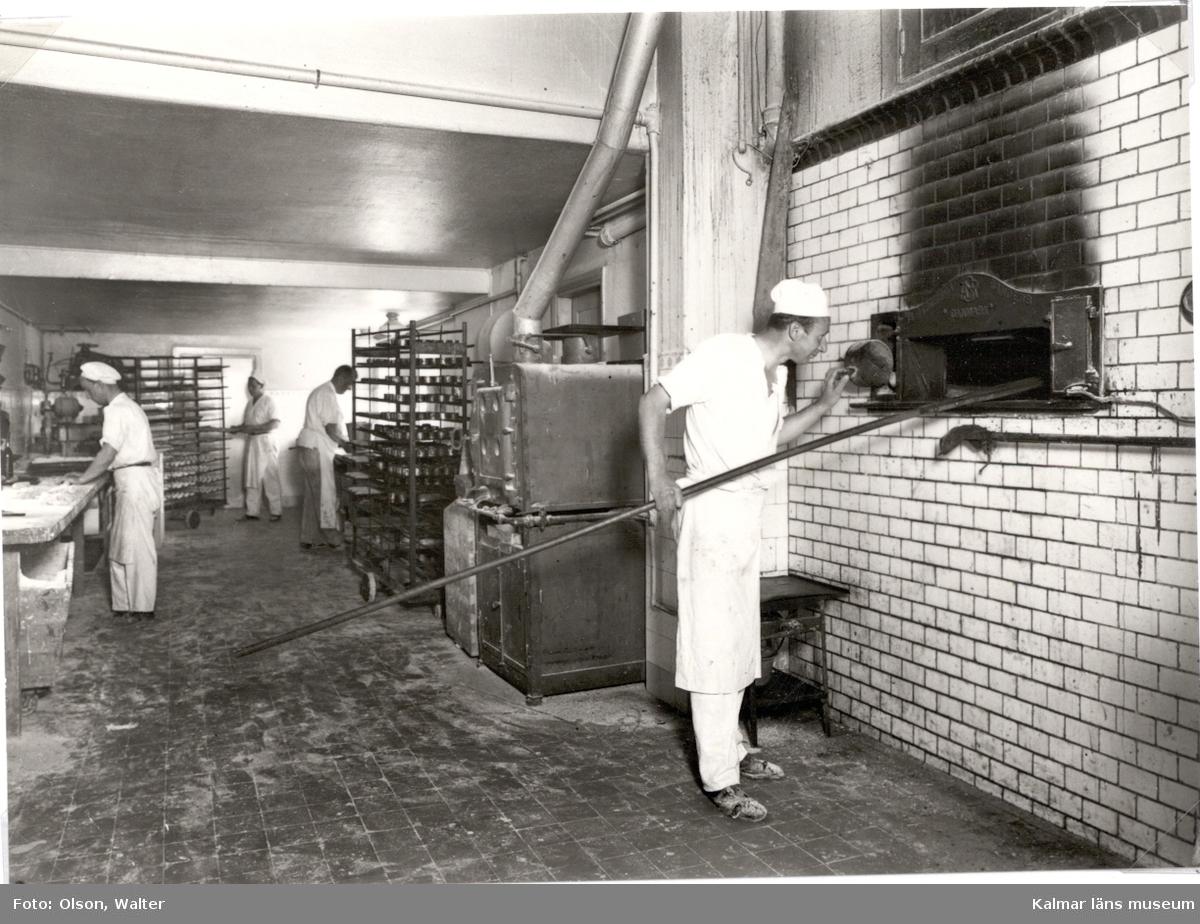 Kalmar Bageriförening. Män som arbetar med bröd, en man står och håller i en brödspade riktad in i en ugn.