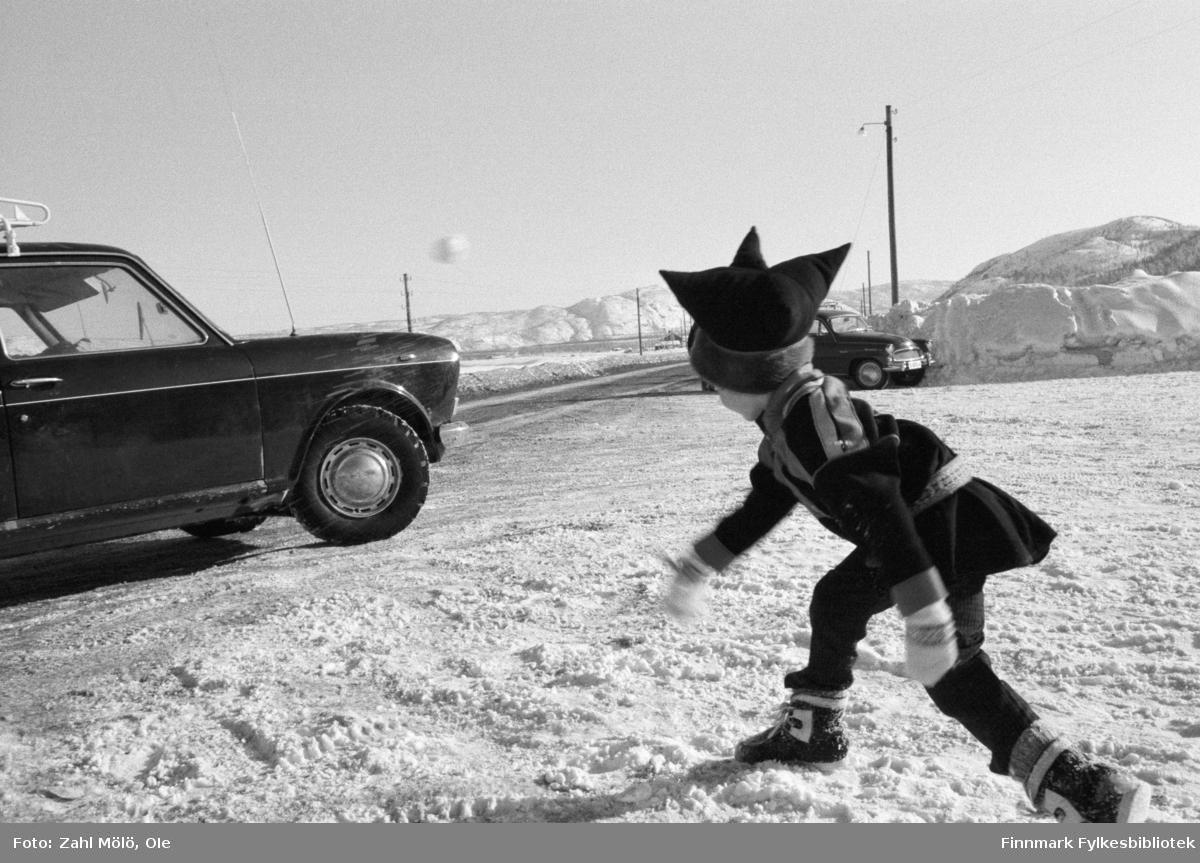 Fotoserie av fotograf Ole Zahl Mölö.  Finland, Nuorgam1968. Liten samisk gutt med stjernelue kaster en snøball. Ole Zahl Mölö, også kjent som Zahl Møller under hans tid i Vadsø – med kunstnernavnet OZAM – er født 8.juli i 1937, i Vadsø. Fotoarkivet har ca. 7500 negativer av Ole Zahl Mölös arbeider i sin samling. Bildematerialet inneholder motiv fra Vadsøs lokalmiljø og gjenspeiler hans hverdagsliv i byen og bymiljøet i vekst på 1960-70-tallet.