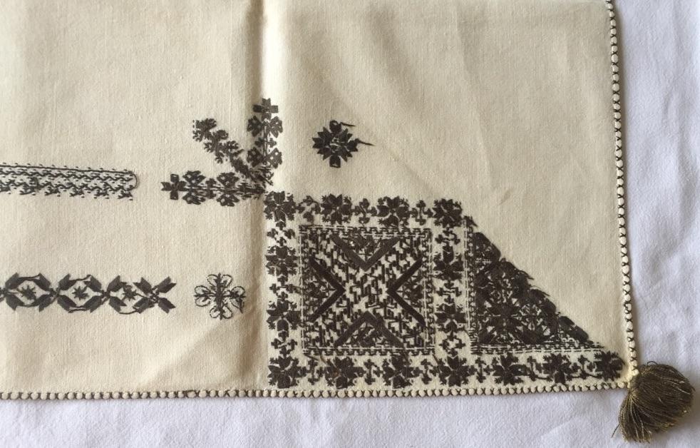 Blomsterliknande mönster i kvadraterna och i bården runt kvadraterna. Geometriskt mönster i plattsöm i några kvadrater. Majstångsspira med slingor i kedjestygn. Två bårder mellan ryggsnibb och framsnibbarna. En med blomstermönster och en i korsstygn. Ornament i plattsöm och kedjestygn.