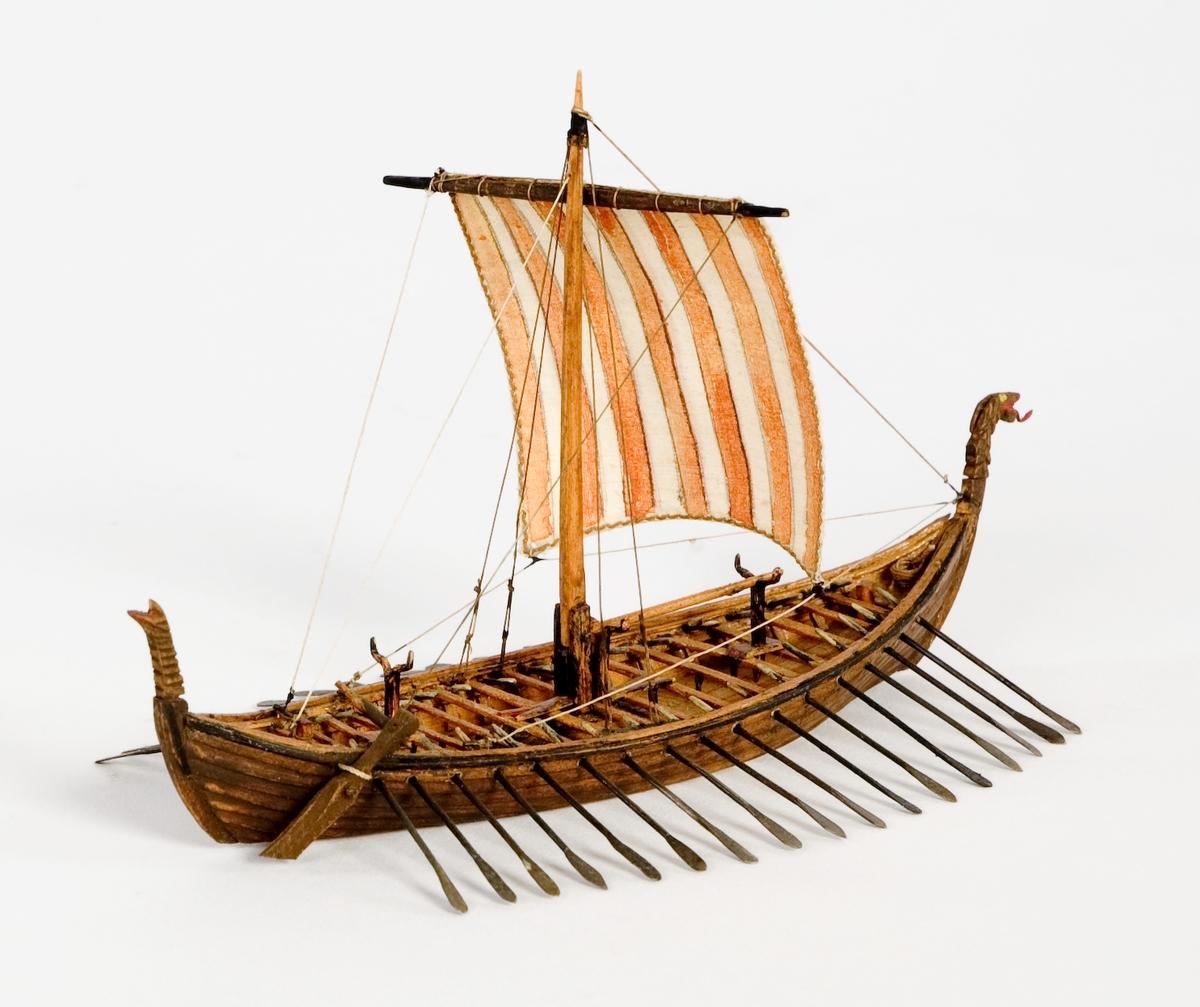 """Fartygsmodell, vattenlinjemodell, hel i block av trä, vikingaskepp (""""Osebergsskeppet"""") 800-t. Klinkbyggd, brunt skrov med höga stävar. Riggad med 1 mast, vit- och rödrandigt råsegel. I förstäven drakhuvud. Utrustad med 17 par åror samt styråra (sidoroder).Föremålets form: Vattenlinjemodell"""