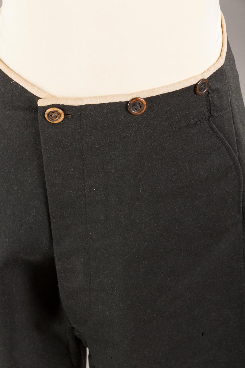 Form: Bena utvidet nederst. Lerretskant rundt livet, spensel i ryggen, mangler spenne i sepnsel? Delvis foret. To lommer. 5 knapper, mangler en knapp.