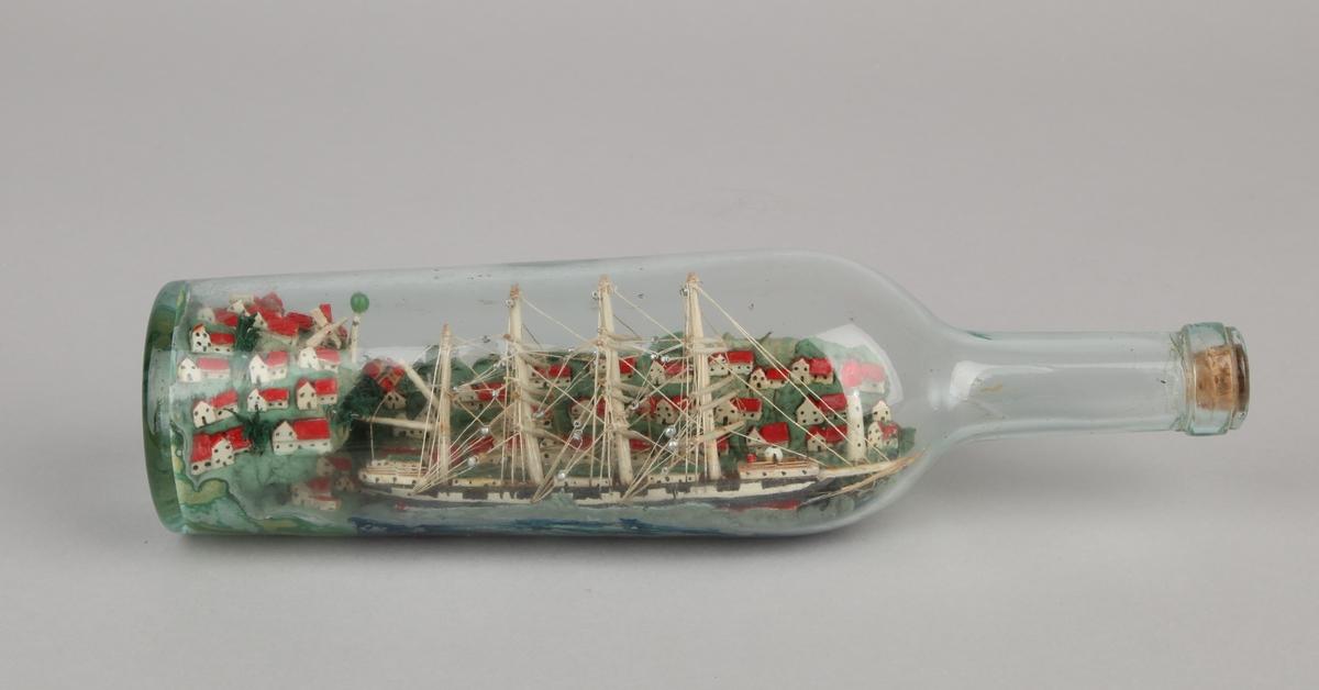 Flaskeskute med fullrigget seilskip ved havn. Ser mange små hvite hus med røde tak, vindmølle og fyrtårn.