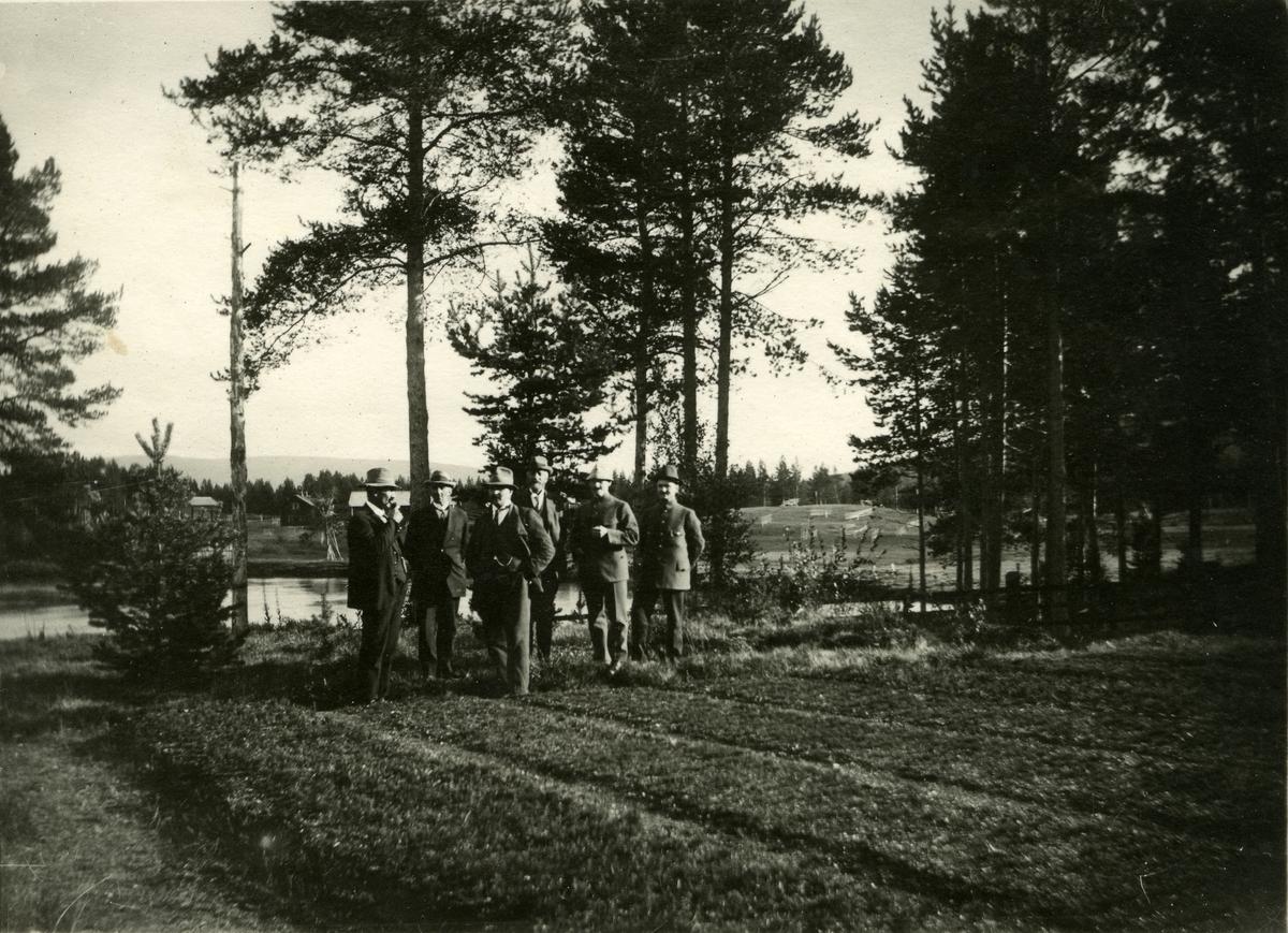 Gruppe menn stående ved åker/plantefelt i Ljørdalen. Vann/elv i bakgrunnen. Adolfsnes planteskole