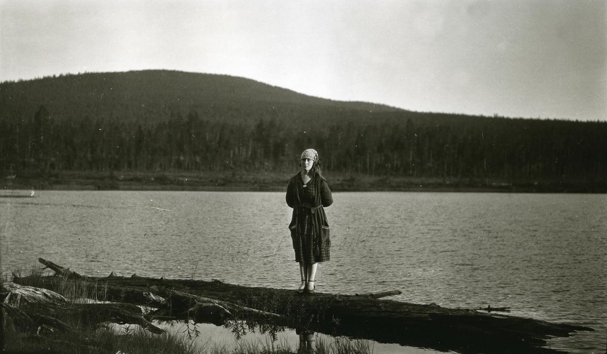 Kvinne stående på trestamme ved innsjø (Flersjøen)