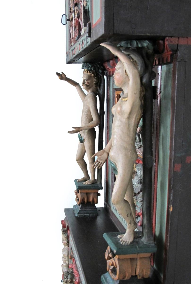 Karyatider, blomster og frukter  i relieff. Døren har  kjerubhode med to apekatter omkring en  fruktkurv under.  frittstående  Adamfigur tv. og en Eva th. som karyatider for overskapet.  Figurene er nakne med grønne fikenblad,  lys karnasjon, plassert på grønne sokler med oker volutter.  (Figurenes armer er nye). apostelen Lukas tv.   med nøkkel gjennom oksen og apostelen  Johannes  ø. th. med   englehode  imellom dem og   ørnen  under engelen. Nedre halvdel har et kjerubhode med store vinger.  Under en  putto med hevet pokal på en tønne, omgitt  av vinranker, fugler og frukter.  På sidene er (nyere) malt røde tulipaner,  de midtre i en vase.  Øverst en bebudelsesscene.