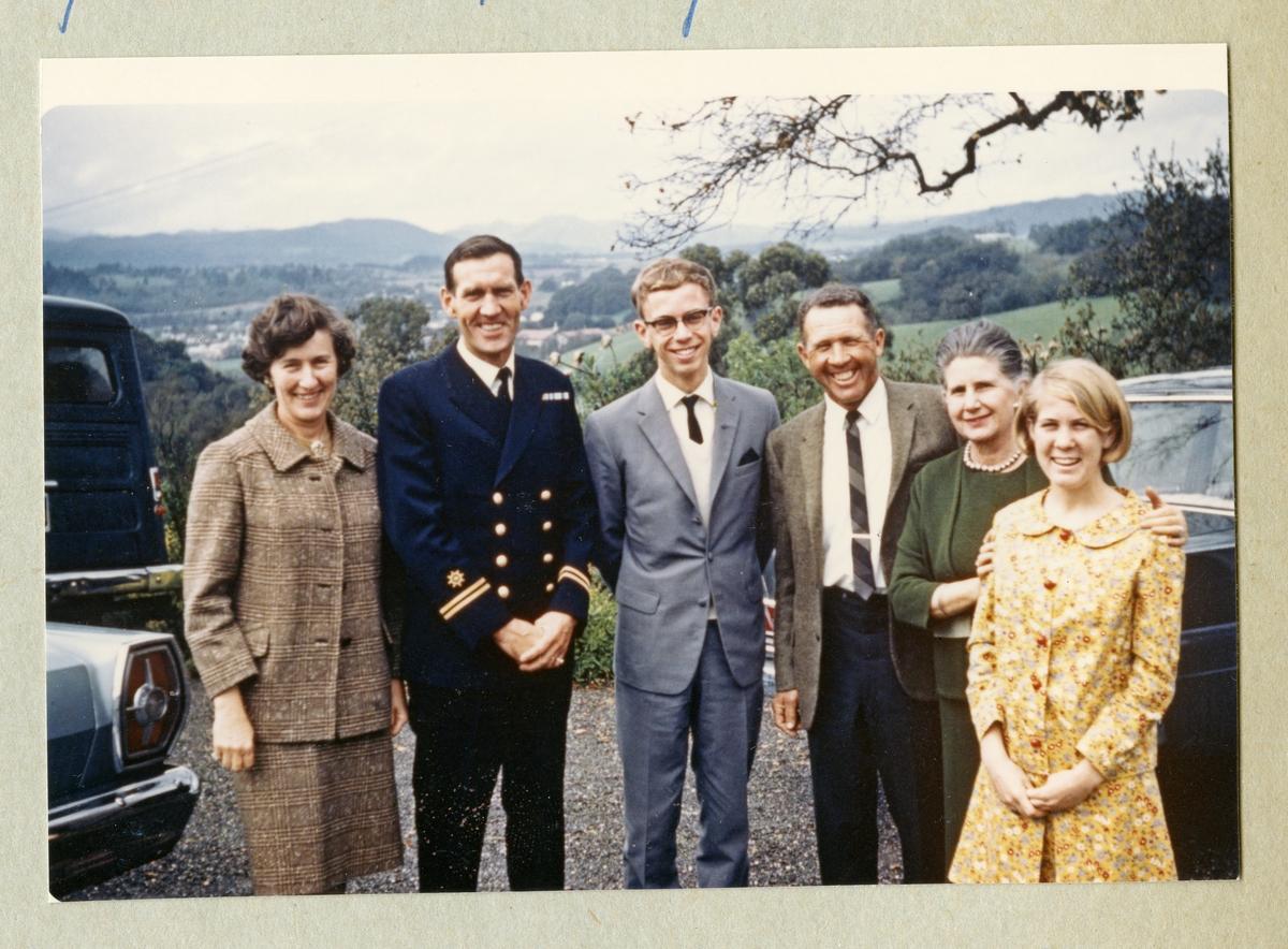 Bilden föreställer ett gruppfoto med Oskar Linde klädd i marinblå uniform tillsammans med två kavajklädda män och tre kvinnor. I bakgrunden skymtar ett grönområde. Bilden är tagen under minfartyget Älvsnabbens långresa 1966-1967.