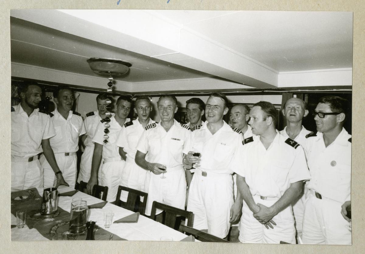 Bilden föreställer sommaruniformsklädda män som har mottagning i minfartyget Älvsnabbens mäss under långresan 1966-1967. Troligen är det gunrummet som här har fungerat som mäss.