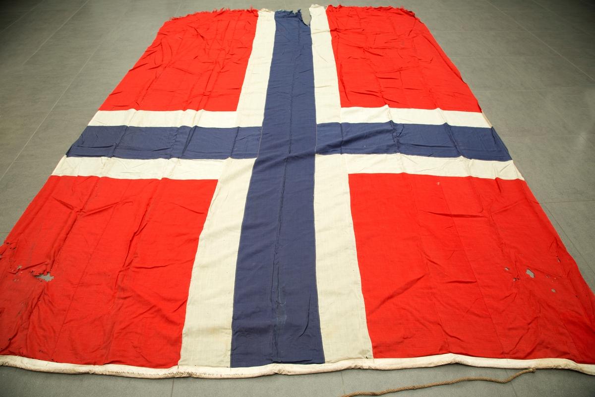 Flaggpose med flagg. A) pose i jute med tau. B) norsk flagg, meget slitt i enden motsatt stangfestet.