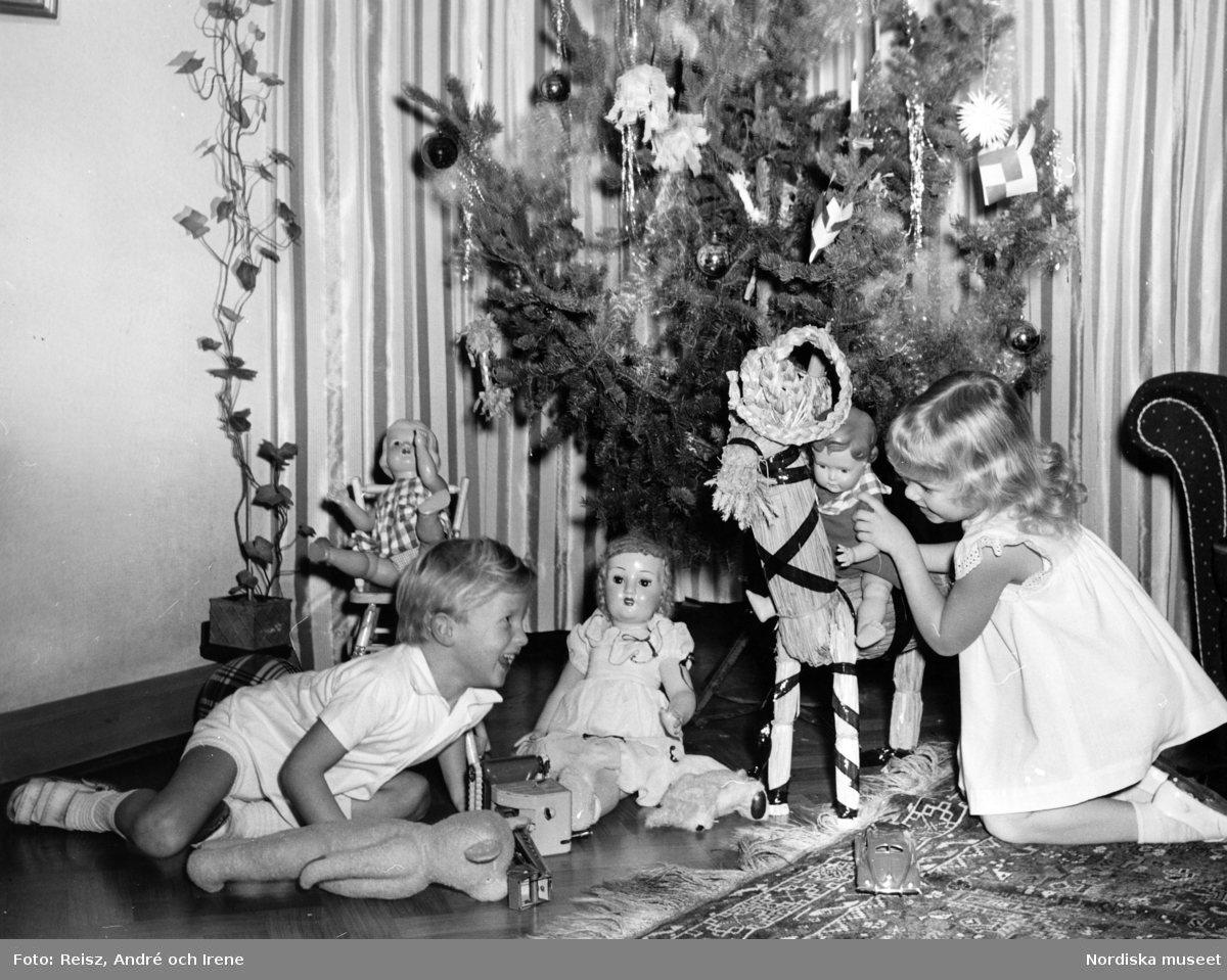 Pojke och flicka med diverse leksaker vid en julgran