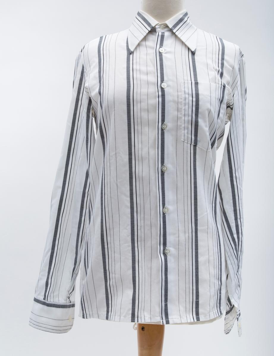 Herreskjorte. Hit med sorte striper, innsvinget med krage, dobbelt skulderstykke. Loddrette striper, brystlomme.