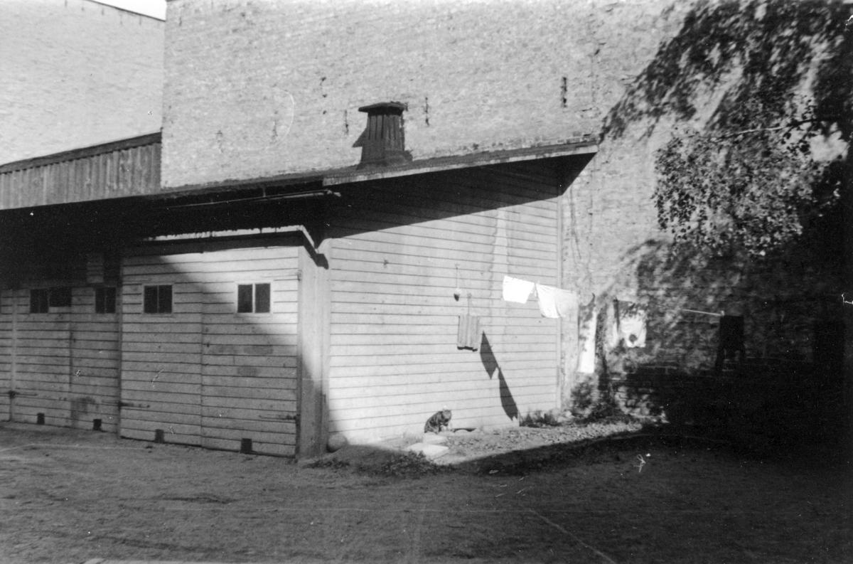 Gårdsinteriör från kvarteret Tunnan i Norrköping. Bilden visar uthuslänga tillhörande Repslagaregatan 23. Fotografiet är taget i samband med rivningsansökan 1953.  Vy mot nord.