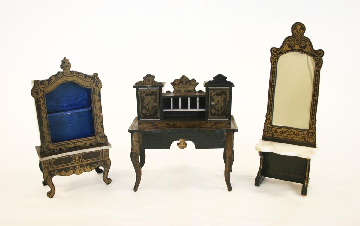A) Skrivebord: Forgylt mønster på bordbena, bordplate, skapdører og kronene. Kineseridekor med våpenskjold på bordplaten og skapdørene med videre utforminger i to blomster. De utkjærte kronene har påmalt krone på.  B) Kabinett med kineseridekor på både understellet og rammet rundt hyllen.  C) Konsollspeill med kineseridekor langs hele rammen rundt speilet. Forgylte stripe på bordbenene.