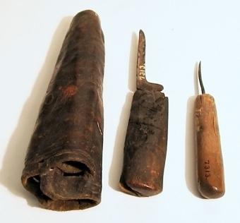 Fodral eller slida för tre olika redskap. Mycket tjockt och kraftigt läder ihopvikt som en strut och ihopsytt på baksidan. Fodralet indelat i tre olika fack. Slidan är öppen i spetsen. En enkel bård upptill på slidan är inpräglat i lädret. En stor och några små röda färgfläckar finns på slidan. I fodralet finns en kniv och en syl, tredje facket är tomt.