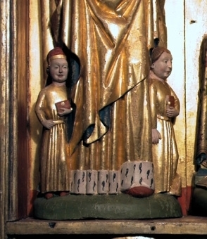 Altarskåp. Skåpets motiv är Den heliga släkten med de tre Mariorna i halvskulptur.   I mitten sitter en krönt jungfru Maria på tron med Jesusbarnet på knät. till vänster står Maria Kleofas, med sönerna Judas Taddeus, Barnabas, Simon och Jacob den yngre. Till höger står Maria Salome, med sönerna Johannes och jacob den äldre. I medaljonger under sockeln återges kvinnornas respektive män: Josef, Kleofas och Salome.   Mittskulpturen är krönt och frontalt sittande på tron med grön kudde. Manteln är förgylld med blå insida över en förgylld tunika. Kronan har tinnar och fyra blomformade applikationer. Karnationen är ljus med röda kindrosor och håret brunt. Skorna röda och marksockeln är grön. Barnet sitter på högerknät med ett röd-grönt äpple i handen och är vänt åt sidan. Klädedräkten är försilvrad.   Den vänstra skulpturen är frontalt stående med ett barn på varje arm och två vid fötterna. Manteln är förgylld med blå insida över förgylld tunika med hermelinmönstrad kant nertill. Vit turban över vitt dok och vitt halslinning. Skon är röd. Marksockeln är grön. Ett barn är naket med äpple i handen och ett barn har röd mantel. Två barn har förgyllda klädedräkter med röda böcker.  Den högra skulpturen är frontalt stående med ett barn på varje arm. Manteln är förgylld med blå insida över en förgylld tunika med hermelinmönstrad kant. Skon är röd. Doket är vitt och halslinningen är vit med ett rött mönster. Ett barn har förgylld tunika med bälte och en uppslagen bok i knät. Det andra barnet har försilvrad tunika och en röd bok.  Skåpets ramverk har en profilerad framkant med bladmetall och blå bemålning. Insidan är röd och utsidan mörkröd liksom sockelns översida. Ryggstycket har en mittnisch, är förgyllt och har glorior ovanför skulpturerna och nertill en röd kant. Masverket är genombrutet och består av krabbor, kölbågar, hängkonsoller och strävpelare som bildar tre nischer över skulpturerna. Gallerverket med tre medaljonger förställer tre frontala halvfigurer skurna i relief m