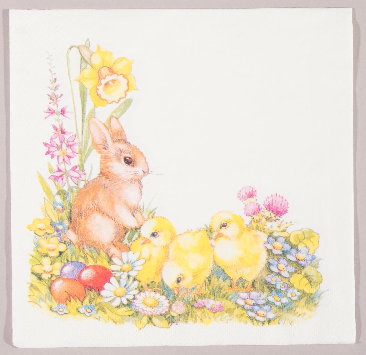 En kanin og tre kyllinger i en blomstereng med påskelilje og andre vårblomster og tre kulørte påskeegg.