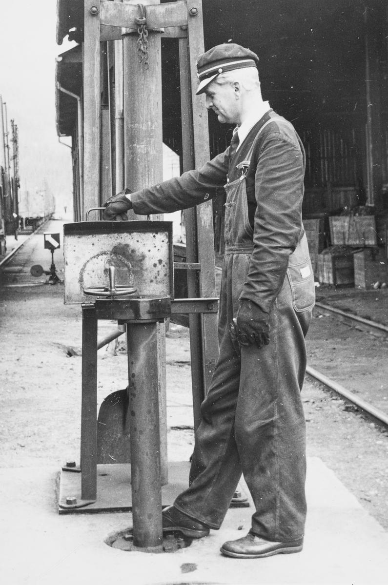 Lokomotivfyrbøter Georg Jensen betjener vannstenderen på Gudå stasjon.
