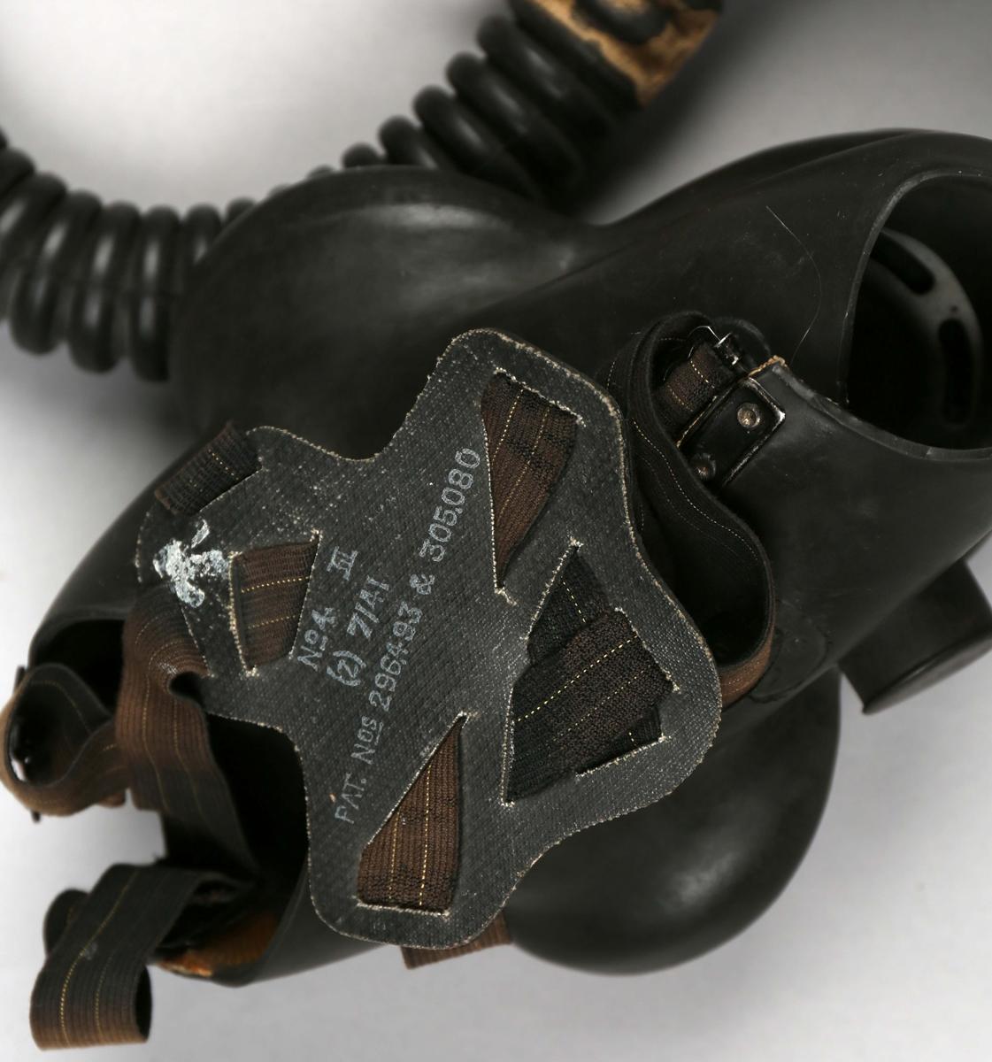 Gassmaske i tøyveske. Gassmaske i gummi med beholder av metall som er koblet sammen med en fleksibel slange. Oppbevares i tøyveske.