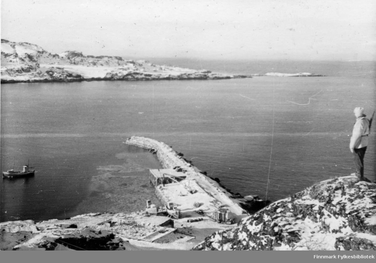"""En soldat fra 2.Bergkompani står vakt på en høyde over snedekket landskap, han har skaller på bena.  Stedet er Holmefjord, Porsanger, 1944/45. I bakgrunnen ser man en branntomt, en lang molo og en fiskebåt. Et par fiskebåter ligger på land. Det kan være m/k """"Glimt"""" av Sørøya som ligger for anker. F64HV - 29fot lang. Før den ble tatt i Sortvik under den såkalte """"Tragedien i Sortvik"""". Båten var i tjeneste under Rognstad og Bergkompaniet og stasjonert i Holmenfjord. Skipper og eier var Johan Eilertsen. Både Johan Eilertsen og Ragnar Jensen mistet livet 21.02.1945, begge fra Breivikbotn.    Bildeserien """"Frigjøringen av Finnmark 1944-45"""" viser et unikt materiale fotografert av soldater i Den Norske Brigade, 2. Bergkompani under deres oppdrag """"Frigjøringen av Finnmark"""" som kom i stand under dekknavn """"Øvelse Crofter"""". Fakta rundt dette bildematerialet illustrerer iflg. vår informant, George Bratli: """"2.Bergkompani, tilhørende Den Norske Brigade i Skottland,  reiste fra Skottland 30. oktober 1944 med krysseren «Berwick» til Scapa Flow på Orkenøyene for å slutte seg til en større konvoi som skulle være med til Norge. Om bord på andre skip var det mange russiske krigsfanger som hadde vært på tysk side og som nå ble sendt hjem.  2.Bergkompani forlot havn 1.november 1944 og kom til Murmansk, Sovjetunionen, 6. november 1944.  De ble her lastet om og fraktet til Petsamo, Sovjetunionen, hvor de ankommer 11.november 1944.  Kompaniet reiser så til Sandnes utenfor Kirkenes og blir forlagt der frem til 26.november 1944. De flytter så videre til Skipparggura.  Den 29.november reiser deler an kompaniet til Rustefielbma og Smalfjord og noen drar opp på Ifjordfjellet.   17. desember ankommer resten av kompaniet til Smalfjord. 30.desember blir en avdeling sendt til Hopseide og 8. januar 1945 blir noen sendt til Kunes. Den 14. januar er kompaniet delt og ligger i Kunes, Kjæs, Børselv, Hopseide og Smalfjord. 5. februar 1945 blir 3.tropp sendt over Porsangerfjorden for å operere i Olderfjorden"""
