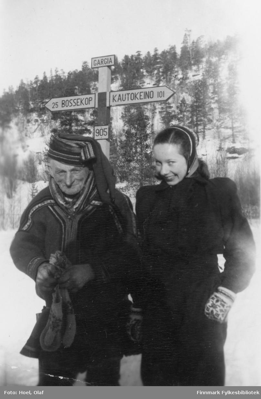 En kvinne og en eldre samisk mann foran et veiskilte i Gargia. En serie med 14 fotografier av landsgymnasets vintertur til Gargia Fjellstue rundt 1950. Til Bossekop-markedet samlet seg samene med sleder og reinsdyr ved Gargia Fjellstue.  Olaf Hoel (1903-1970) var den første rektoren ved fylkets første gymnas Finnmark off. Gymnas i Alta i årene 1948-1952. Kjell F. Hoel har gitt en liten bildesamling etter sin far fra hans tid i Alta til Finnmark fylkesbibliotek. Olaf Hoel gjorde en pionerinnsats for skolen under gjenreisningen av landsdelen etter krigen.