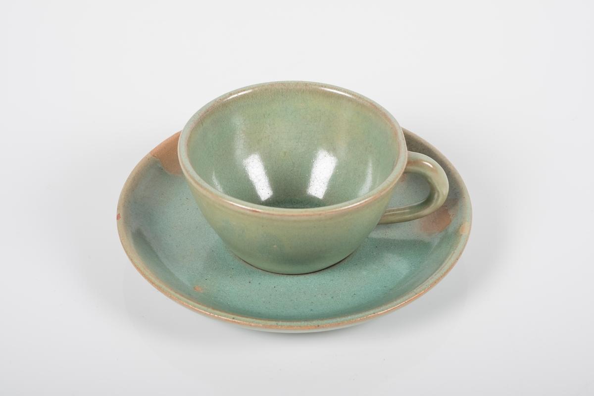 Kopp med skål i keramikk med grønn lasur. Buet hank på koppen. Tre små knotter på undersiden av koppen, usikker funksjon. Skålen har spor etter tre knotter på bunnen, usikker funksjon.