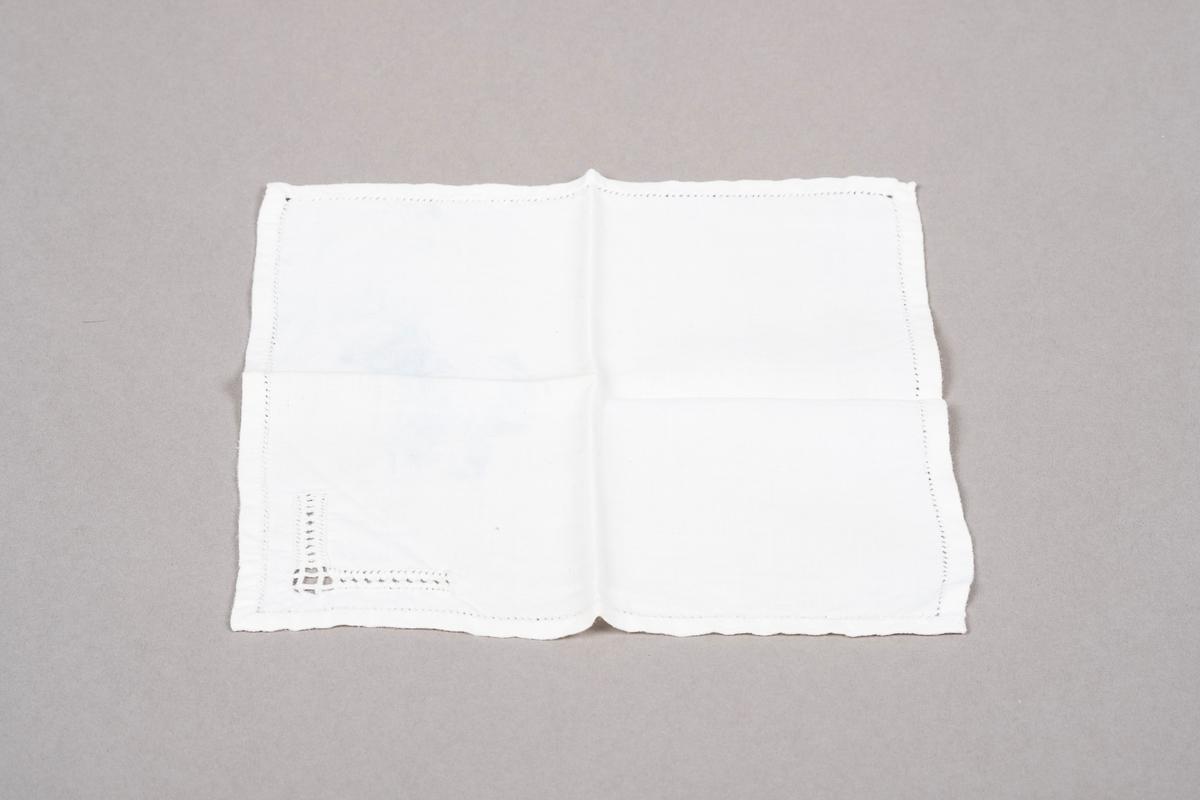 Hvit lommetørkle i bomull med hullbroderier. En blek blå flekk.