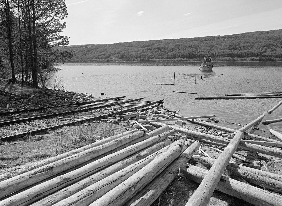 Sjøsetting av tømmerslepebåten «Storsjø» på innsjøen den var oppkalt etter i Rendalen i Hedmark.  Fotografiet er tatt våren 1984, som var den siste fløtingssesongen i denne delen av Glommavassdraget.  I vintersesongen lå båten i opplag på en slipp ved den såkalte «Dampbåtvika» på østsida av Storsjøens nordende.  Her var det lagt en skinnegang på tresviller i en slak skråning ned mot sjøen og et stykke videre under vannflata (til venstre i dette bildet).  På denne skinnegangen gikk det ei vogn med jernbanehjul.  Vogna var forankret i en kraftig vaier med forbindelse til en vinsj et stykke oppe på land.  Ved hjelp av denne vinsjen kunne vogna, med båten som last, kjøres kontrollert ned mot sjøen eller opp igjen på tørt land.  Da dette fotografiet ble tatt sto vogna ute i vannet, der bare stenderne på sidene stakk opp over vannspeilet, mens fartøyet fløt fritt.  I forgrunnen lå det en del værslitt lensetømmer.  Direksjonen (styret) for Christiania Tømmerdirektion (Glomma fellesfløtingsforening) vedtok i 1911 å gå til anskaffelse av en dampslepebåt som kunne brukes til å trekke tømmer i bommer over den lange og djupe Storsjøen. Her hadde det vært vanskelig å få fløtt fram virket i løpet av en sesong, noe som innebar verdiforringelse av tømmeret. Det nye fartøyet ble kontrahert fra Glommens mek. Verksted i Fredrikstad. I mangel av farbar vannveg mellom verftet og sjøen der båten skulle brukes ble komponentene fraktet med tog til Koppang. Derfra ble de trukket på sleder over til Burua i Ytre Rendalen, hvor komponentene ble klinket sammen. Båten ble satt i drift våren 1912 og gikk som tømmersleper i Rendalen fram til 1984.  Mer informasjon om denne slepebåten og det transportsystemet den inngikk i finnes under fanen «Opplysninger».